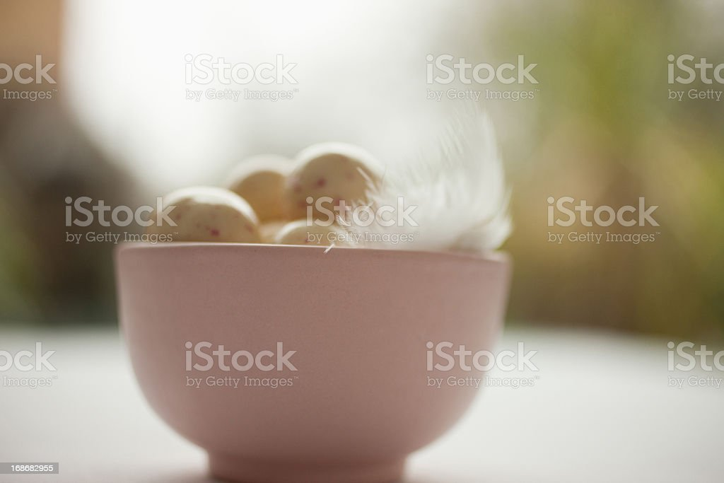 Speckled candy eggs in bowl with feather royalty-free stock photo