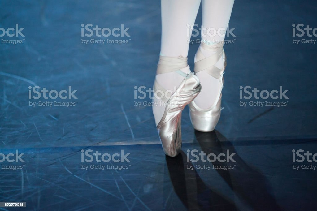 spectacle, dancing, equipment concept. two small aesthetic feet in beautiful pink pointe shoes of ballerina, dancing on the scratched floor of the theater stage stock photo