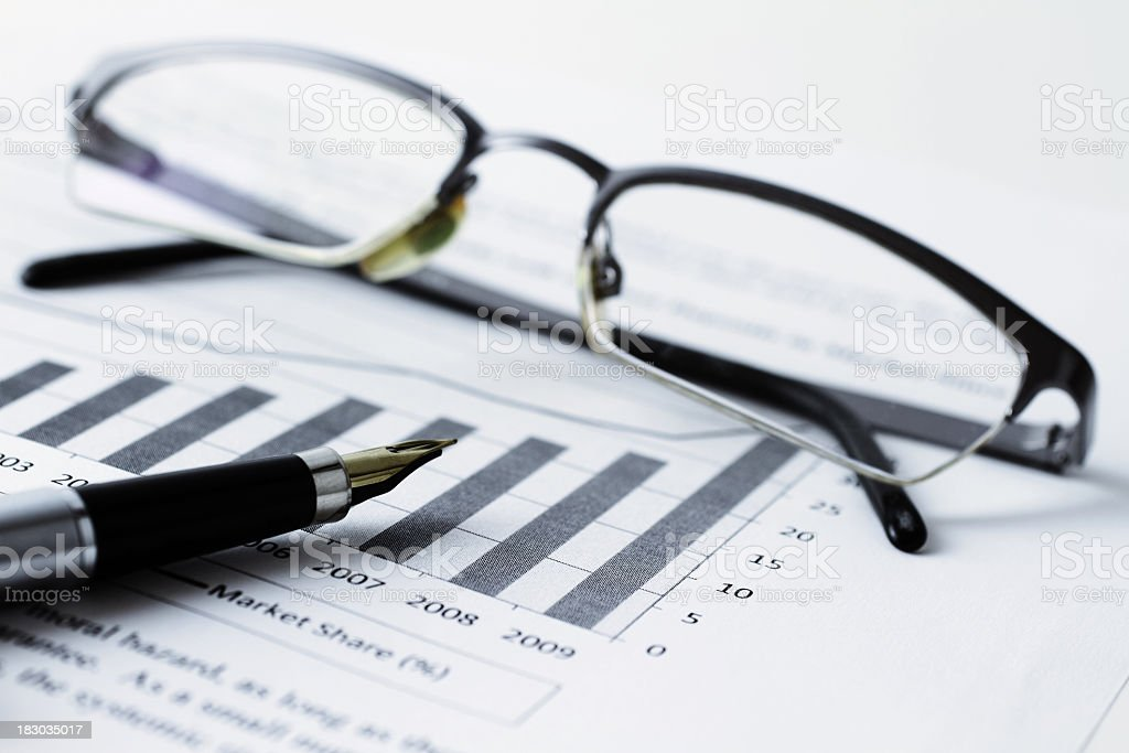 Spectacles and pen on top of a bar chart document royalty-free stock photo