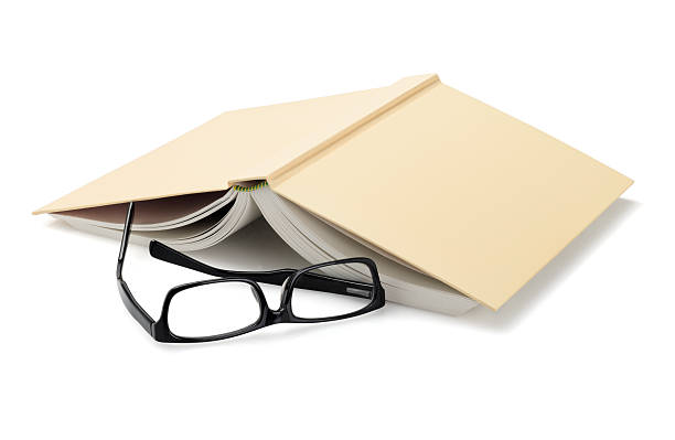 Spectacles Beside Inverted Book Spectacles Beside Inverted Book On White Background face down stock pictures, royalty-free photos & images