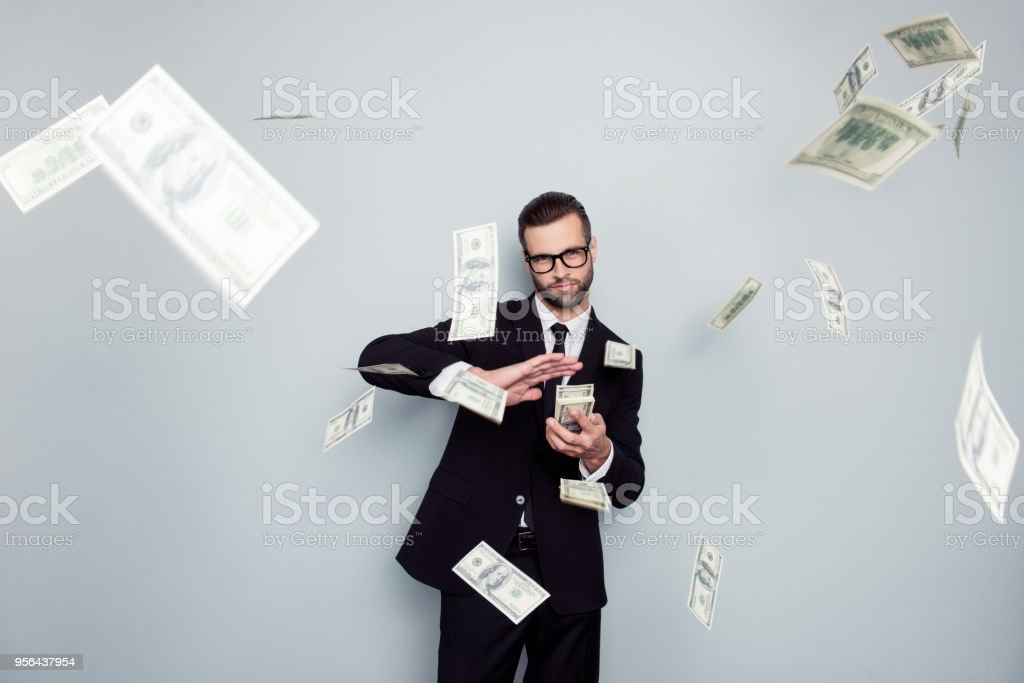 Spectacles jackpot entrepreneur economist banker chic posh manager jacket concept. Handsome confident cunning clever wealthy rich luxury guy holding wasting stack of money isolated on gray background stock photo