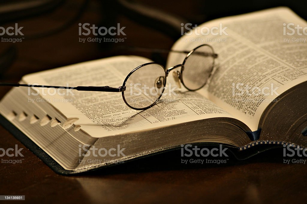 Spectacles resting on a page of an open book stock photo