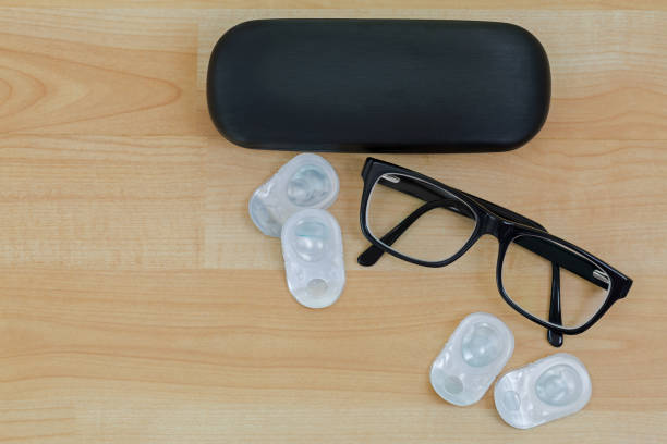 Spectacles with black frame, eye glasses case next to pairs of new contact lenses on wooden background stock photo