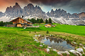 Amazing alpine landscape with high peaks, wooden chalets and mountain lake. Famous Geisler - Odle peaks in background at sunset, Alto Adige, Dolomites, Italy, Europe