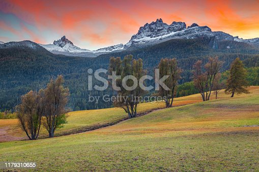 Picturesque autumn landscape with snowy peaks at sunset. Autumn rural landscape with colorful sunset near Cortina d Ampezzo touristic town, Dolomites, Italy, Europe