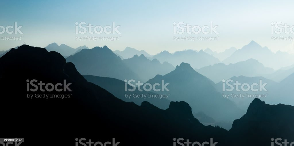 Spectacular blue and cyan mountain ranges silhouettes. Summit crosses visible. stock photo