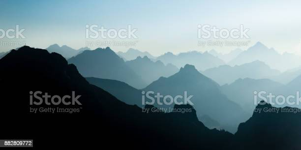 Photo of Spectacular blue and cyan mountain ranges silhouettes. Summit crosses visible.