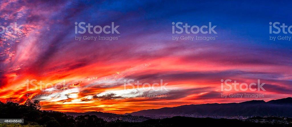 Incendio como espectacular de los edificios de la ciudad al atardecer con los colores vibrantes - foto de stock