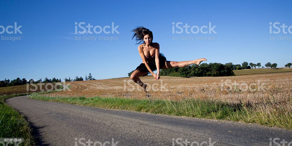 Spectacular jump of a barefoot dancer on a road. stock photo