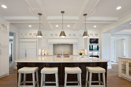 White kitchen with brown island and coffered ceiling
