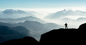 Beautiful view snow covered mountain ranges silhouettes and fog filled valleys with bright back light. South Tyrol, Itay, Alps. Happy winning success man at sunset or sunrise standing relaxed and is happy for having reached mountain top summit goal during hiking travel trek.