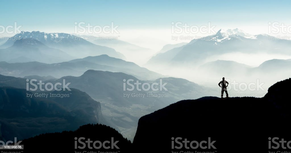 Spectacular mountain ranges silhouettes. Man reaching summit enjoying freedom. stock photo