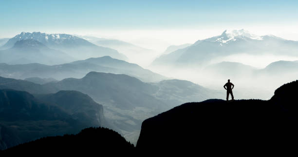 spectacular mountain ranges silhouettes. man reaching summit enjoying freedom. - mountain stock photos and pictures