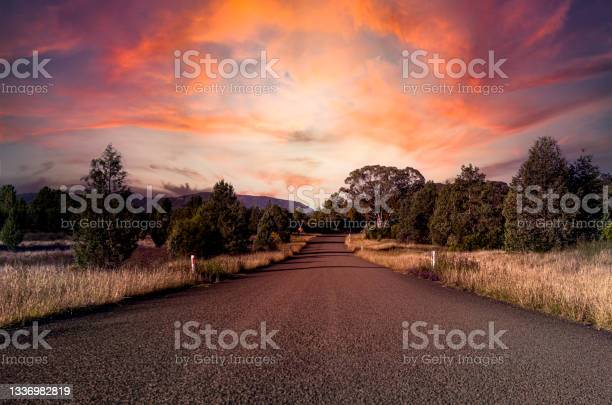 Photo of Spectacular pink glow of sunset on gathering storm clouds and the hilly landscape surrounding a country road in eastern Australia.