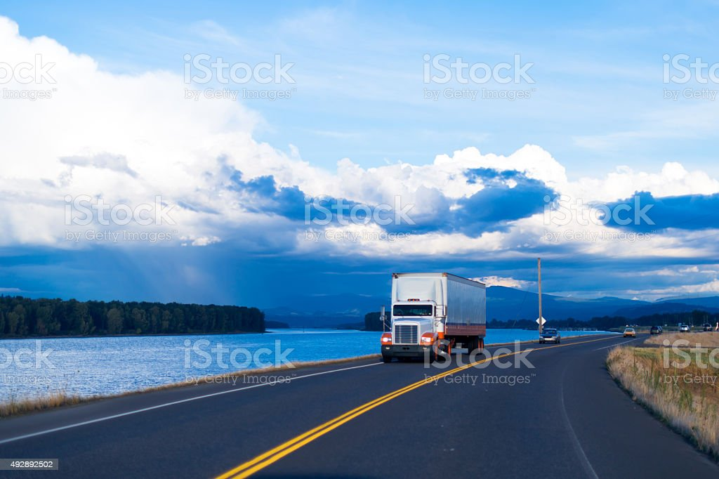 Spectacular river view of road with semi truck and trailer stock photo