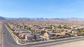 AERIAL Spectacular shot of Las Vegas suburbs sprawling across the Mojave desert. Real estate properties fill up the arid terrain leading up to the city of Las Vegas. Stunning shot of American suburbia