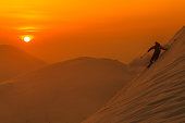 SILHOUETTE: Spectacular shot of pro skier riding off trail on a picturesque sunny evening in Niseko. Unrecognizable male tourist shredding the powder snow covering the beautiful mountains in Japan.
