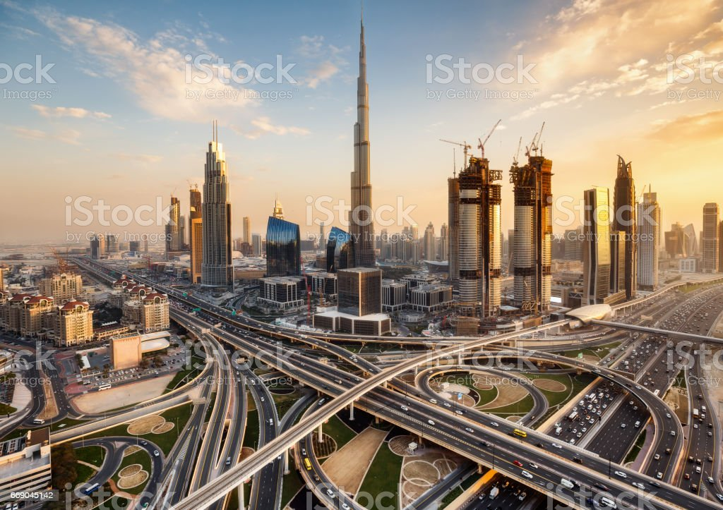 Spectacular skyline of Dubai, UAE.  Futuristic modern architecture of a big city at sunset with a large highway intersection. stock photo