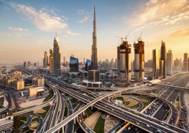 Spectacular skyline of Dubai, UAE.  Futuristic modern architecture of a big city at sunset with a large highway intersection. Spectacular skyline of Dubai, UAE.  Futuristic modern architecture of a big city at sunset. Aerial view. dubai stock pictures, royalty-free photos & images