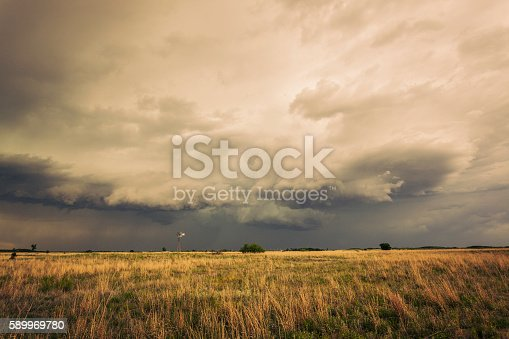 Spectacular storm clouds loom menacingly over a lone windmill (windpump) in grasslands.  The vanes are harnessing energy from the severe storm. Horizontal, copy space, dramatic processing.