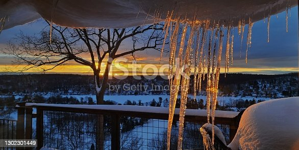 Bright oranges and yellows from the Sun's rays just at the peek of civil light and dawn, reflecting its colors through a large grouping of long icicles within a snowy scene.  Weather icons, travel ideas, peacefulness.