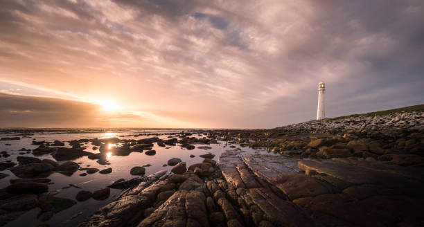 A spectacular sunset at the Slankop lighthouse at Kommetjie in Cape Town, Western Cape of South Africa. stock photo