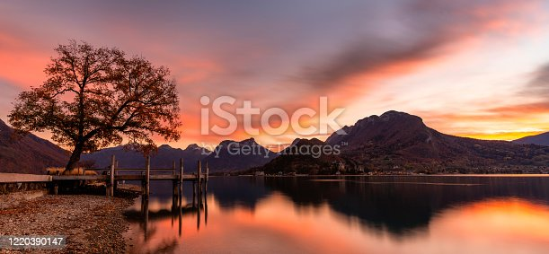 Spectacular sunset in Annecy. Orange and red clouds and a lake in the French Alps