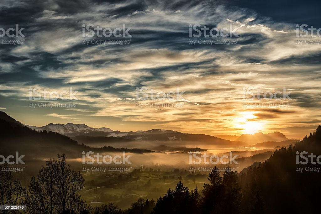 spectacular sunset over landscape at European alps in winter View from Allgäu in Germany (Obersdorf) over the Austrian Vorarlberg till to the Alpstein and Mountain Säntis in Switzerland in the background. 2015 Stock Photo