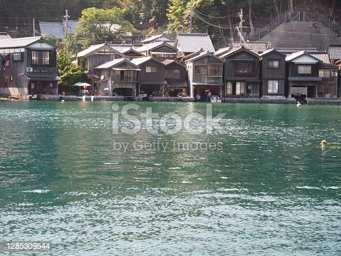 Spectacular view of Sea of Japan coast olf fishing village of Ine in Kyoto prefecture in Japan with old fishing houses, blue sky and turquoise waters of a bay on a sunny day