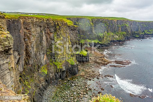 Spectacular view of the rocky cliffs along the coastal walk route from Doolin to the Cliffs of Moher, geosites and geopark, Wild Atlantic Way, rainy day in county Clare in Ireland