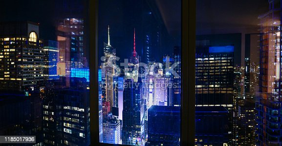 CLOSE UP: Spectacular view of Times Square at night from a luxury hotel room in downtown Manhattan. Bright lights of New York city light up at night. View from the top floor of an apartment building.