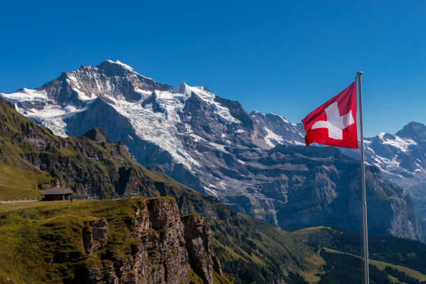 Spectacular view on famous snowcapped Jungfrau from Mannlichen with swiss flag in foreground Spectacular view on famous mountain Jungfrau in Bernese Alps on beautiful day from viewpoint Mannlichen. Lauterbrunnen, Switzerland swiss alps stock pictures, royalty-free photos & images