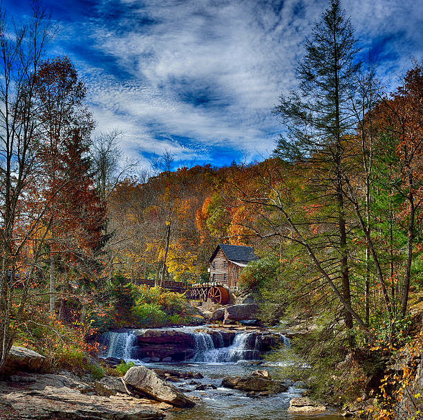 Spectacular vivid fall color Grist Mill Babcock State Park Spectacular vivid fall color at the Glade Creek Grist Mill Babcock State Park, against a vid blue sky with cirrus clouds, processed for dramatic and enchanting presentation. babcock state park stock pictures, royalty-free photos & images