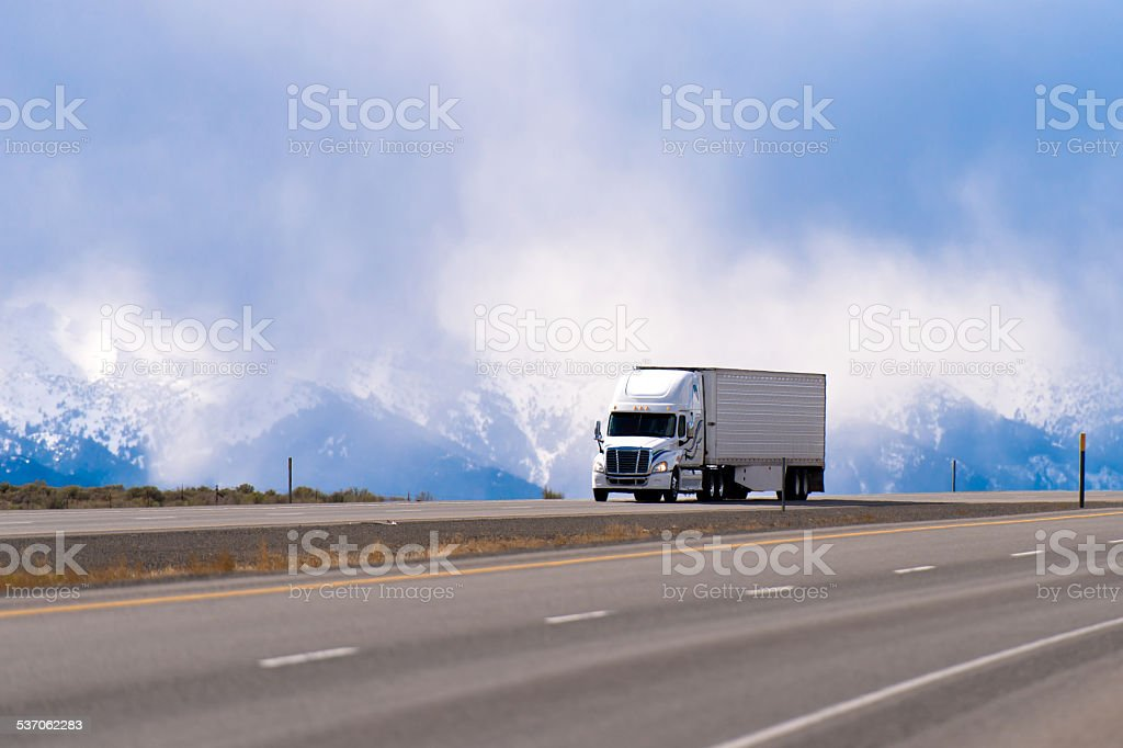 Spectacular white semi truck trailer reefer on highway snow mountains stock photo