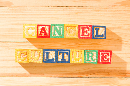 Spectacular wooden cubes with the word CANCEL CULTURE on a wooden surface.