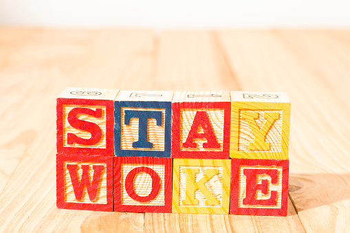 Spectacular wooden cubes with the word STAY WOKE on a wooden surface.
