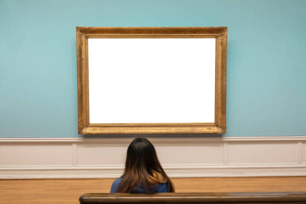 Spectator looking blank large golden frame on blue wall stock photo