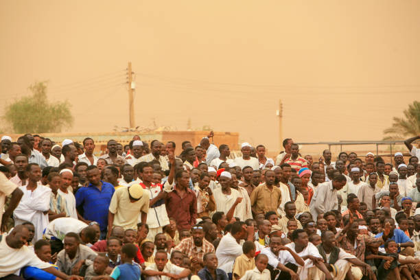 Spectators attending an open air Nubian wrestling gathering in Khartoum, Sudan Khartoum, Sudan - May 28, 2010: Spectators attending an open air Nubian wrestling gathering in Khartoum, Sudan. Every Friday people gather in open public spaces to practice and watch Nubian wrestling. This traditional form of fight is named after the Nubian tribes from Kordofan though it is practiced by people from other ethnic backgrounds too. Khartoum is the capital and largest city of Sudan, located at the confluence of the White Nile, flowing north from Lake Victoria in Uganda, and the Blue Nile, flowing west from Ethiopia. Khartoum is composed of 3 cities: Khartoum proper, Khartoum North and Omdurman. omdurman stock pictures, royalty-free photos & images