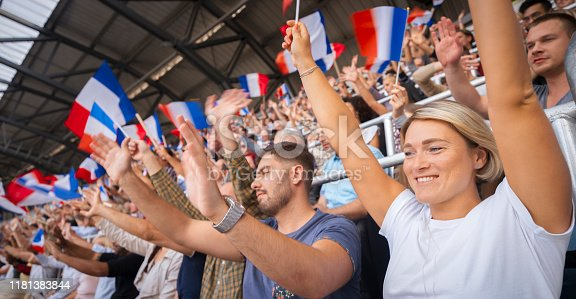 Cheerful spectators raising their arms while watching match in stadium.