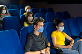 Group of people watching movie in the cinema after Coronavirus loosening measures.