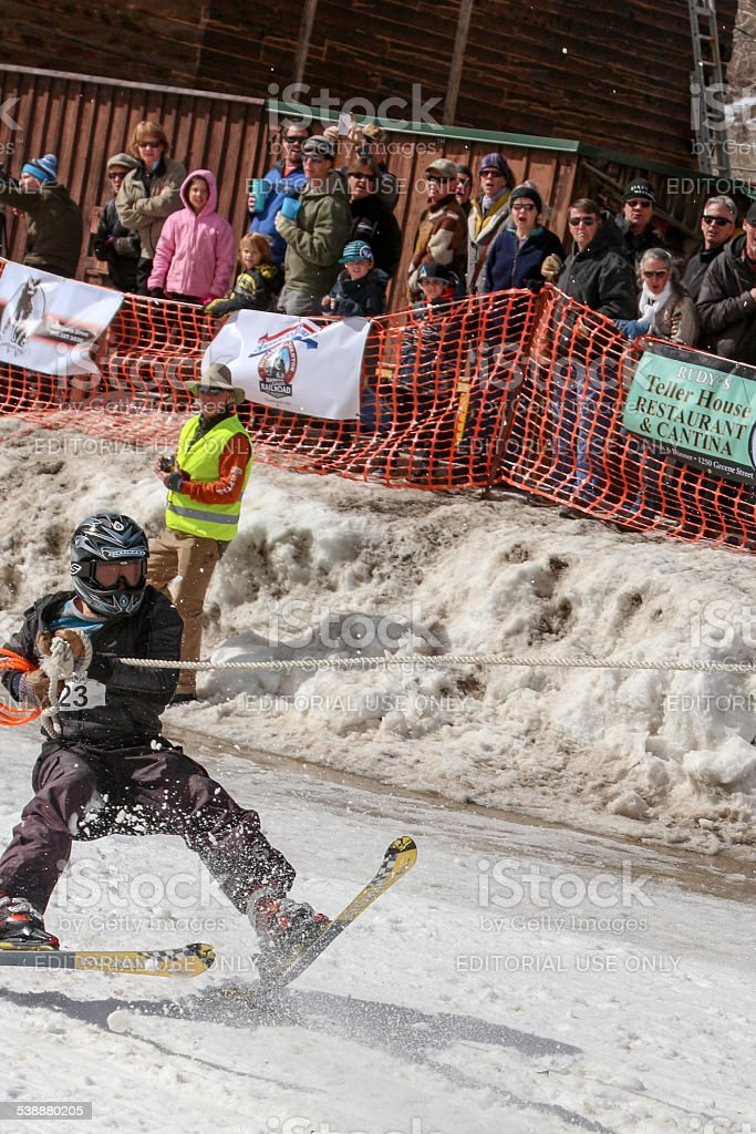 Spectators look on as a skijoring competitor starts to fall stock photo