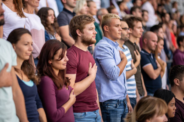 spectators singing national anthem in stadium - national anthem stock photos and pictures