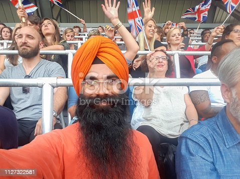 Cheerful male fans taking selfie while watching match in stadium.
