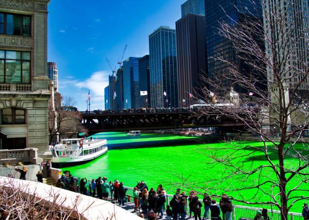 zuschauer sehen den chicago river, die für st. patricks day grün gefärbt ist. - st. patrick's day stock-fotos und bilder