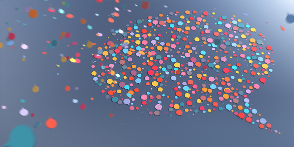 Lots of multi-coloured speech bubble icons falling from above at speed with motion blur, and gathering together to form a larger speech bubble speech on a plain background.