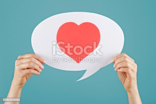 Woman's hand holding white speech bubble, Red heart shape in it.