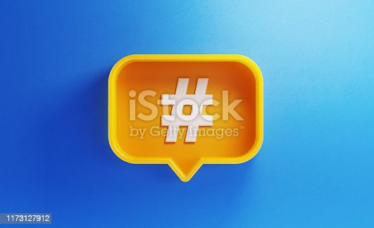 Speech bubble shaped yellow button with hashtag symbol on blue background. Horizontal composition with copy space. Social media and online messaging concept.