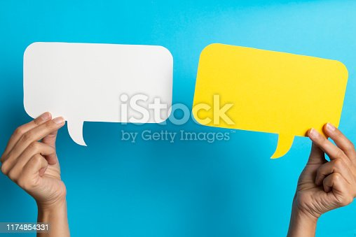 Two hands are holding two speech bubbles which are white and yellow.