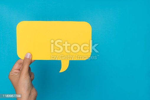Hand is holding one yellow speech bubble in front of blue background.