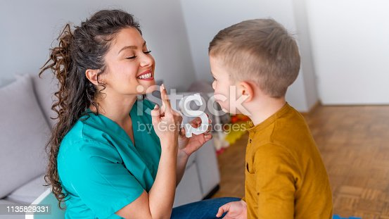 istock Speech therapist and little patient training articulation 1135829331